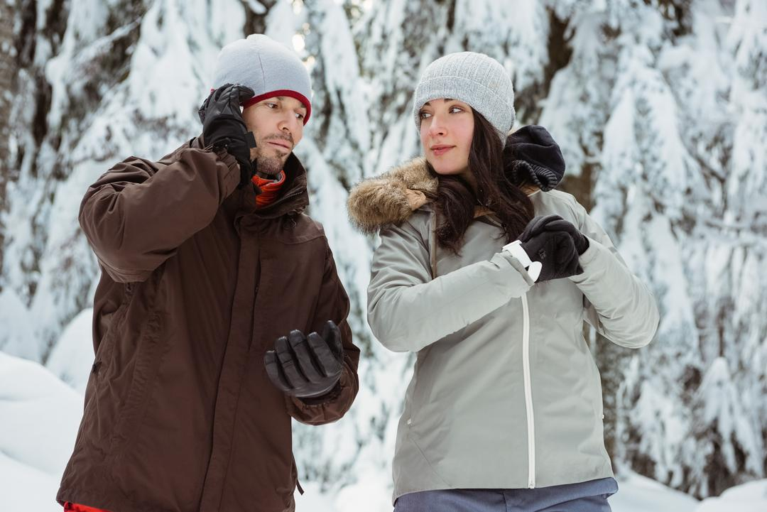 Man talking on mobile phone and woman checking time on snow covered mountain
