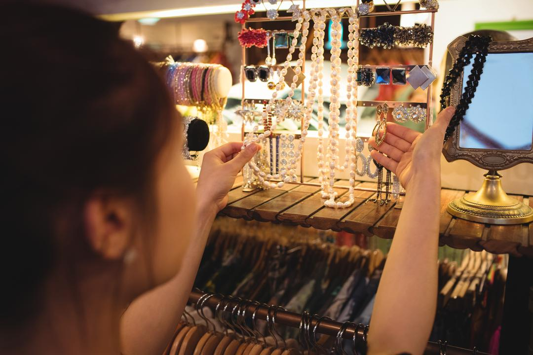 Stylish woman selecting jewellery in a antique jewellery shops