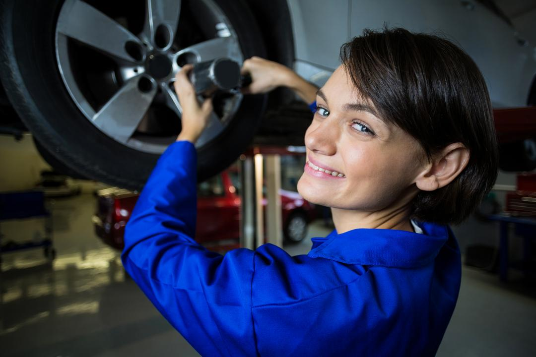 Portrait of female mechanic fixing a car wheel with pneumatic wrench in repair garage Free Stock Images from PikWizard