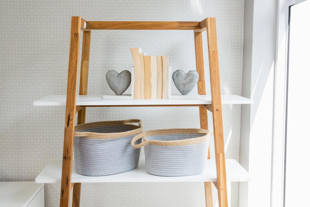 Books, heart shape and basket arranged on shelf in living room at home