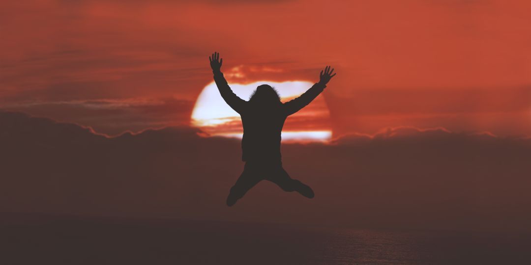 silouette of a person jumping in front of a red sunset