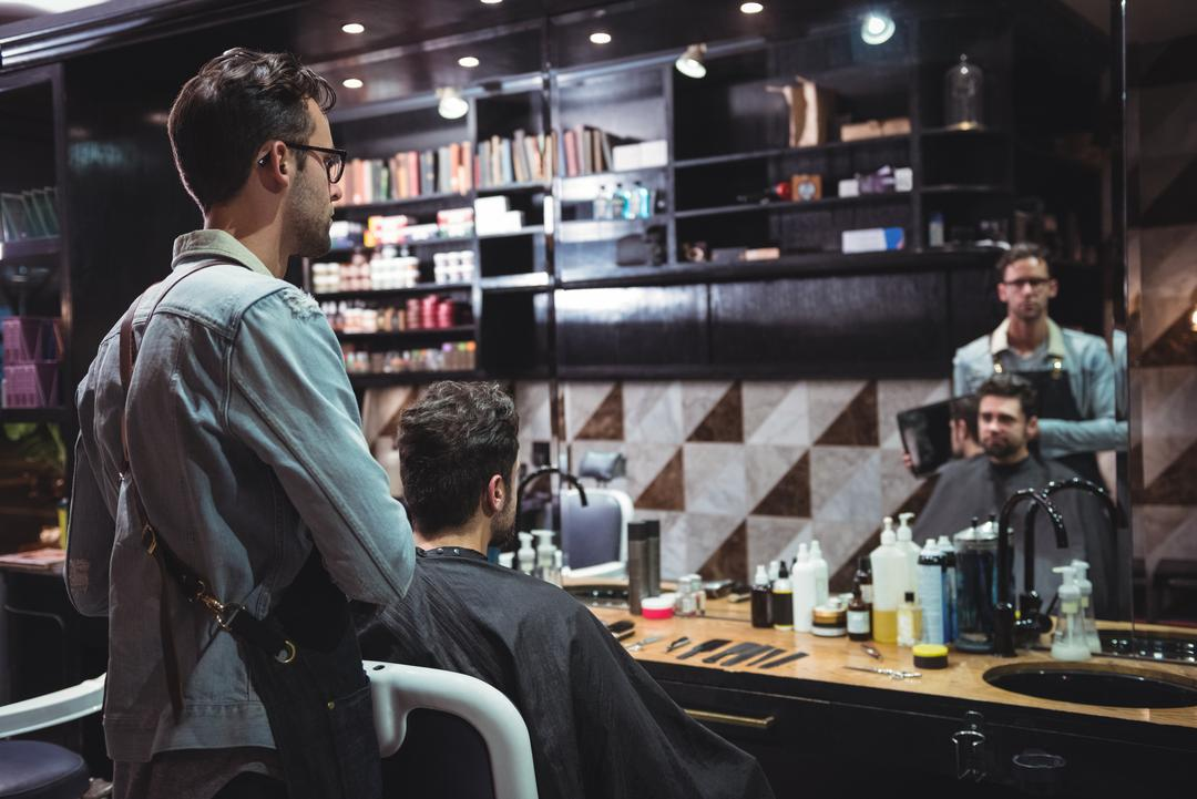 Barber showing man his haircut in mirror in baber shop