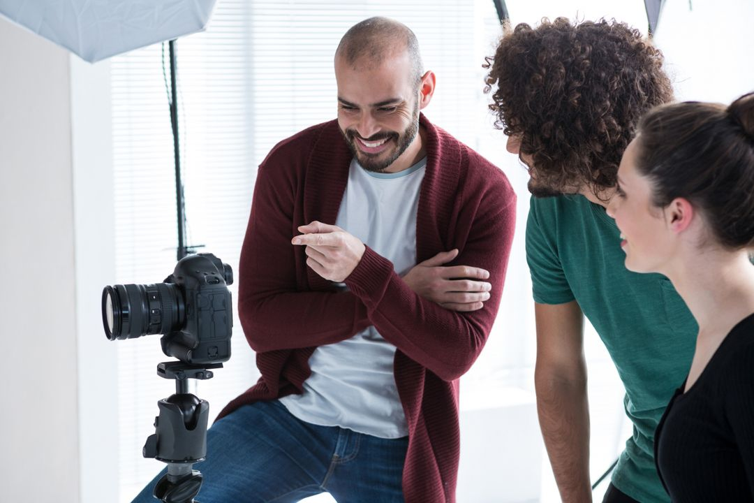 Image of Three People Standing Behind a Camera on a Tripod