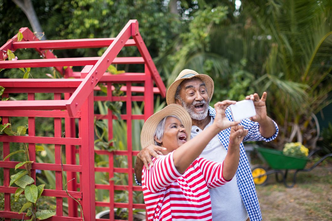 Cheerful senior couple taking selfie while standing in yard