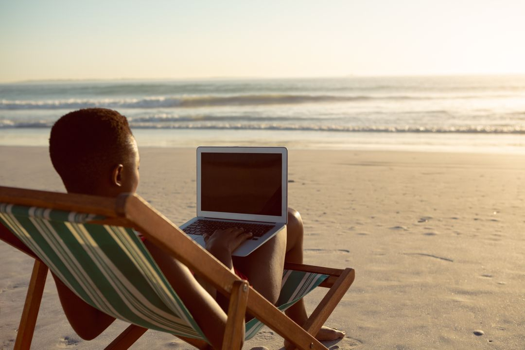 Rear view of woman using laptop while relaxing in a beach chair on the beach