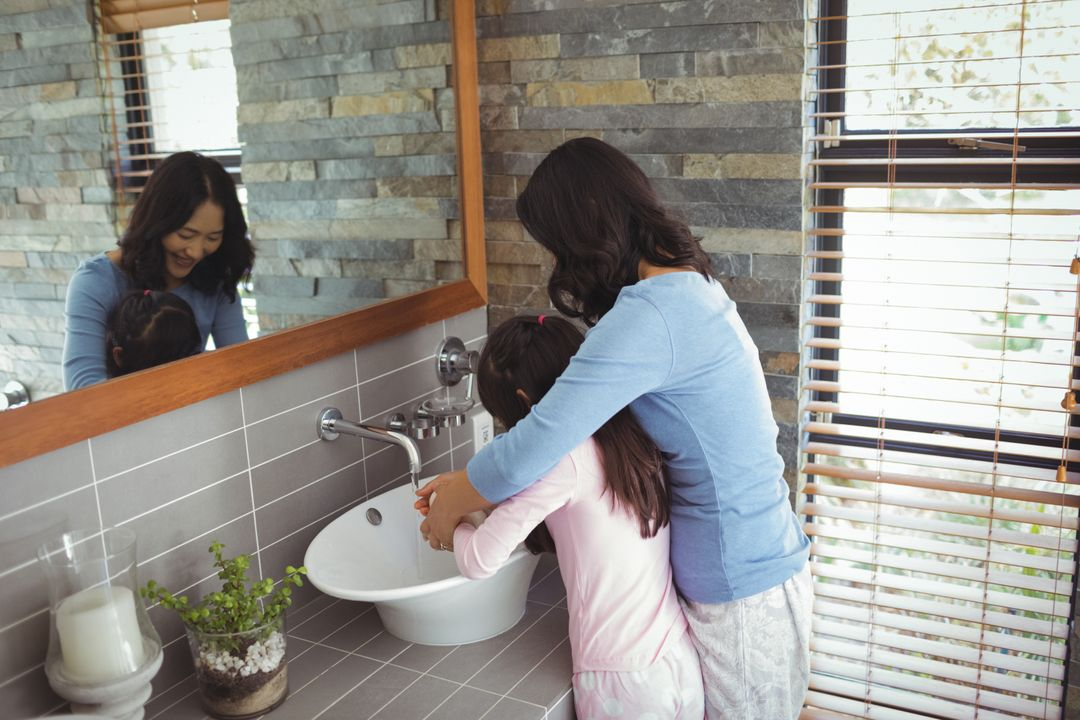 Mother and daughter washing hands in bathroom sink at home Free Stock Images from PikWizard