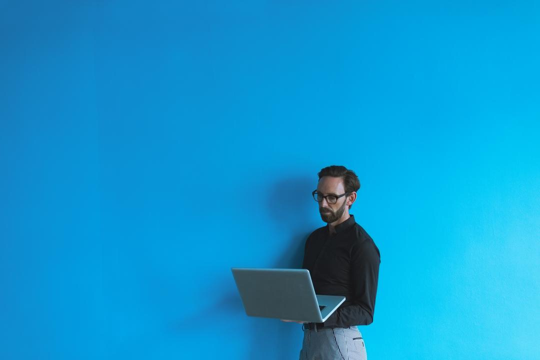Male executive using laptop against blue wall in office