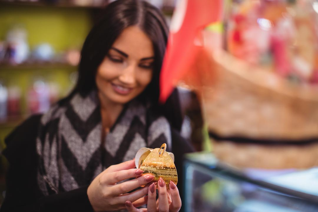 Beautiful woman holding a turkish sweet in shop