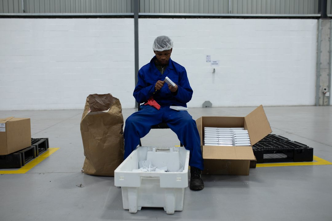Front view of a focused mixed race male worker busy working in a factory warehouse, wearing a hair net and overalls, sitting preparing and packing plastic parts in a cardboard box Free Stock Images from PikWizard
