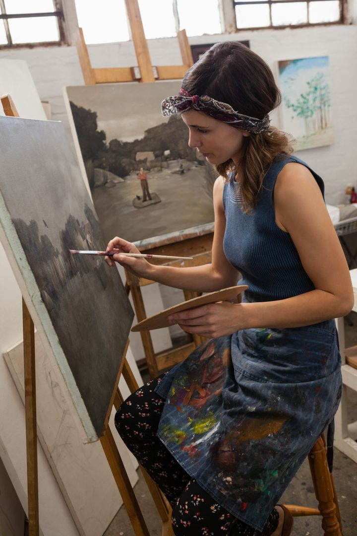 Attentive woman painting on canvas in drawing class Free Stock Images from PikWizard