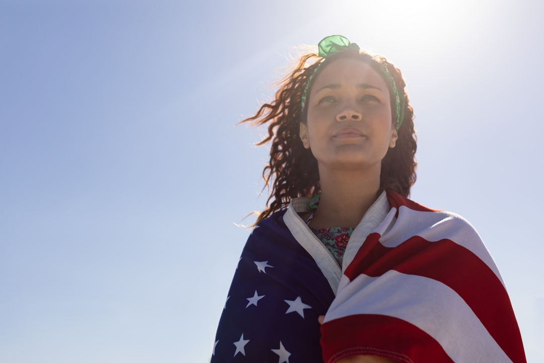 Low angle view of beautiful young Mixed-race woman wrapped in american flag on beach in the sunshine