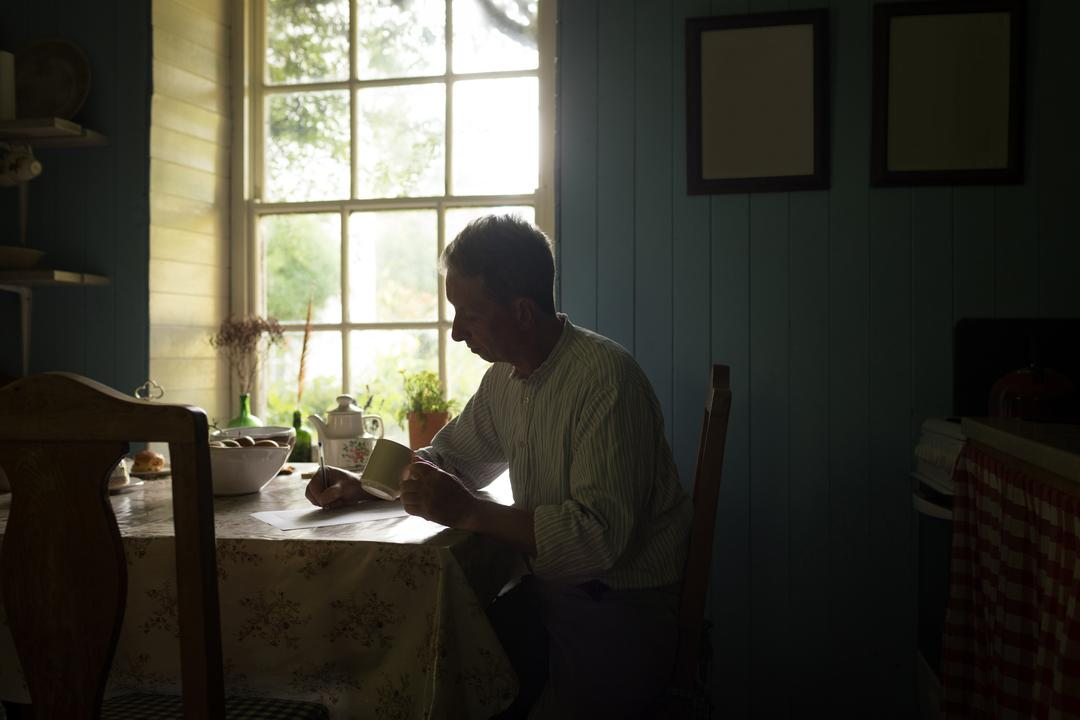 Senior man writing on document while having coffee in kitchen at home