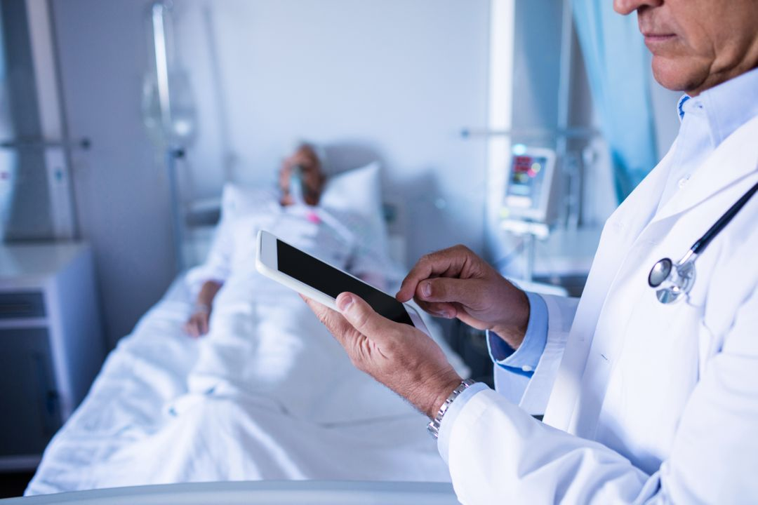 Mid-section of male doctor using digital tablet in the hospital Free Stock Images from PikWizard