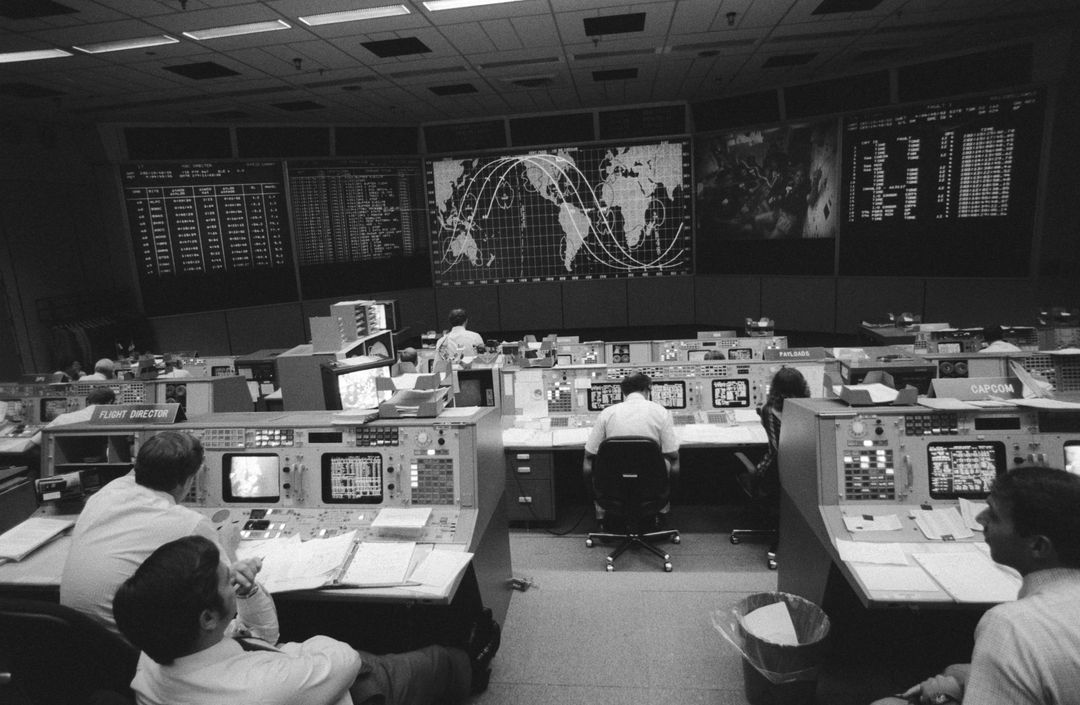 View from the back of the Mission Control Center (MCC). Visible are the Flight Directors console (left front), the CAPCOM console (right front) and the Payloads console. Some of the STS 41-G crew can be seen on a large screen at the front of the MCC along with a map tracking the progress of the orbiter.