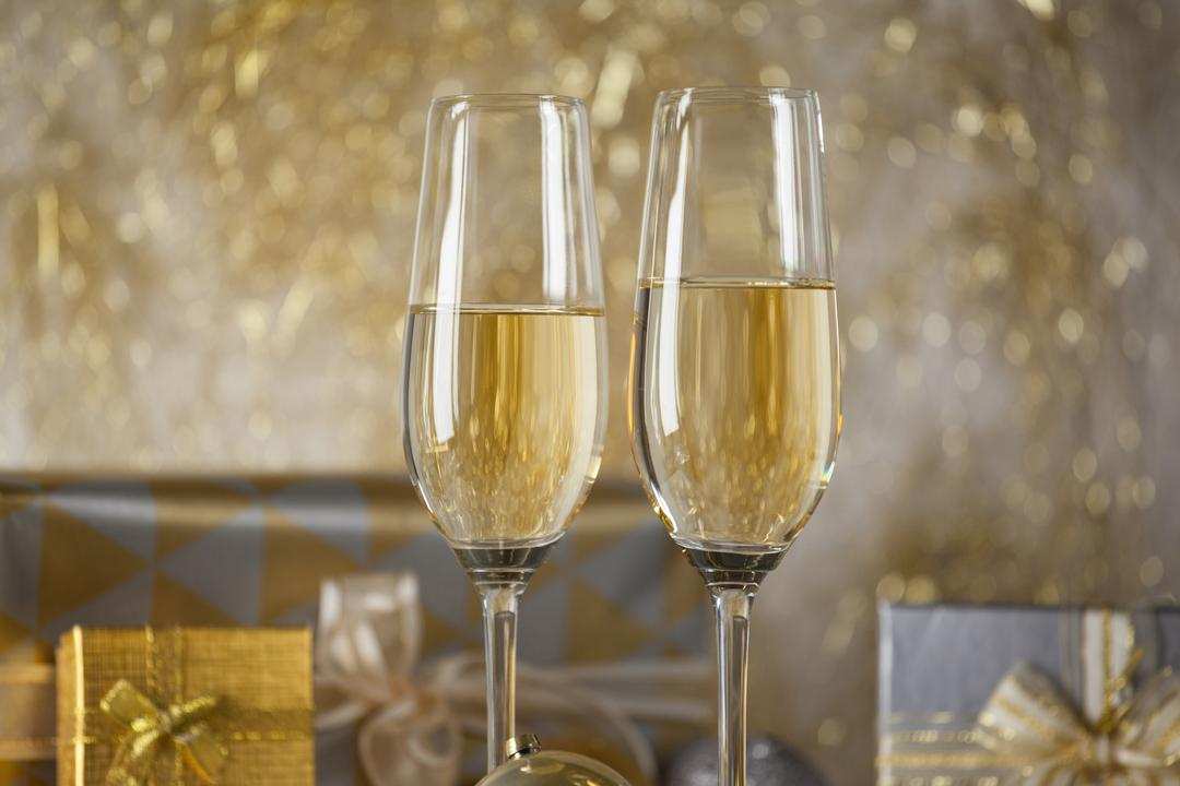 Two champagne flutes and Christmas gifts against golden color decoration