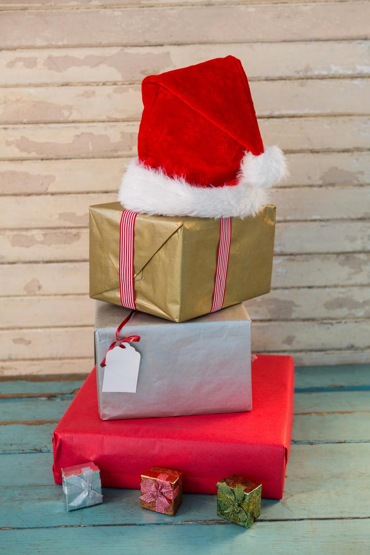 Wrapped gifts and santa hat on wooden plank during christmas time Free Stock Images from PikWizard