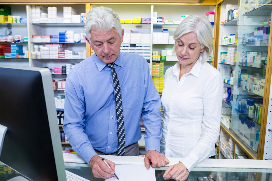 Pharmacist writing prescriptions for medicines in pharmacy Free Stock Images from PikWizard
