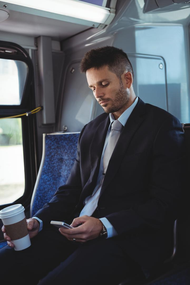 Businessman holding a disposable coffee cup and using mobile phone in the bus