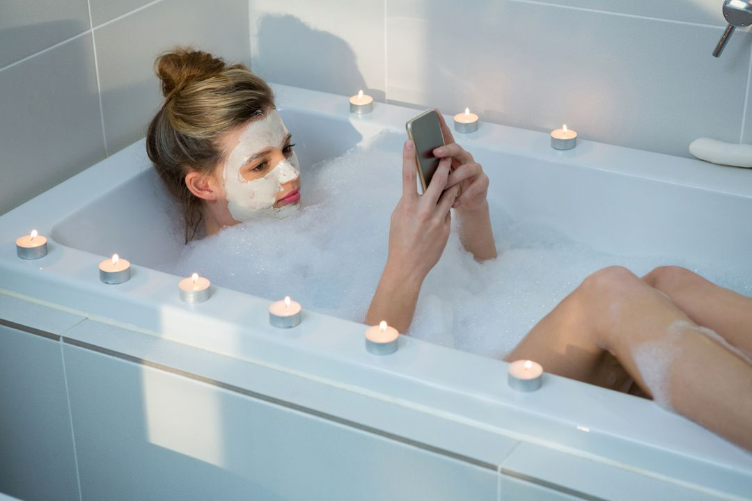 Woman using mobile phone while having bath in bathtub at bathroom Free Stock Images from PikWizard