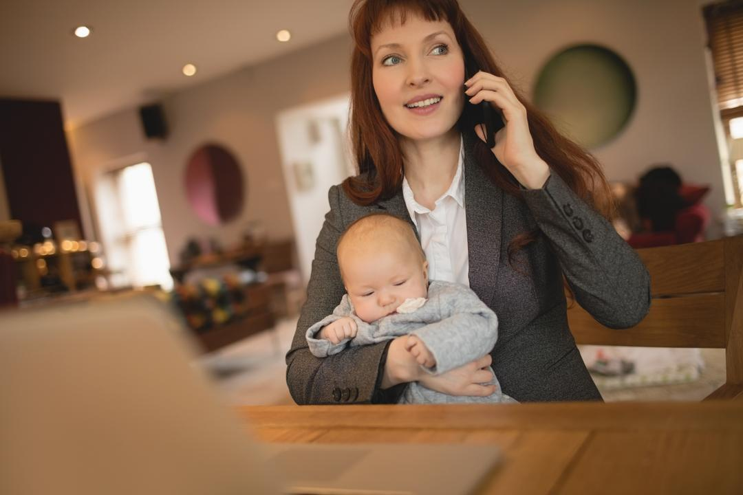 Mother talking on mobile phone while holding her baby at home