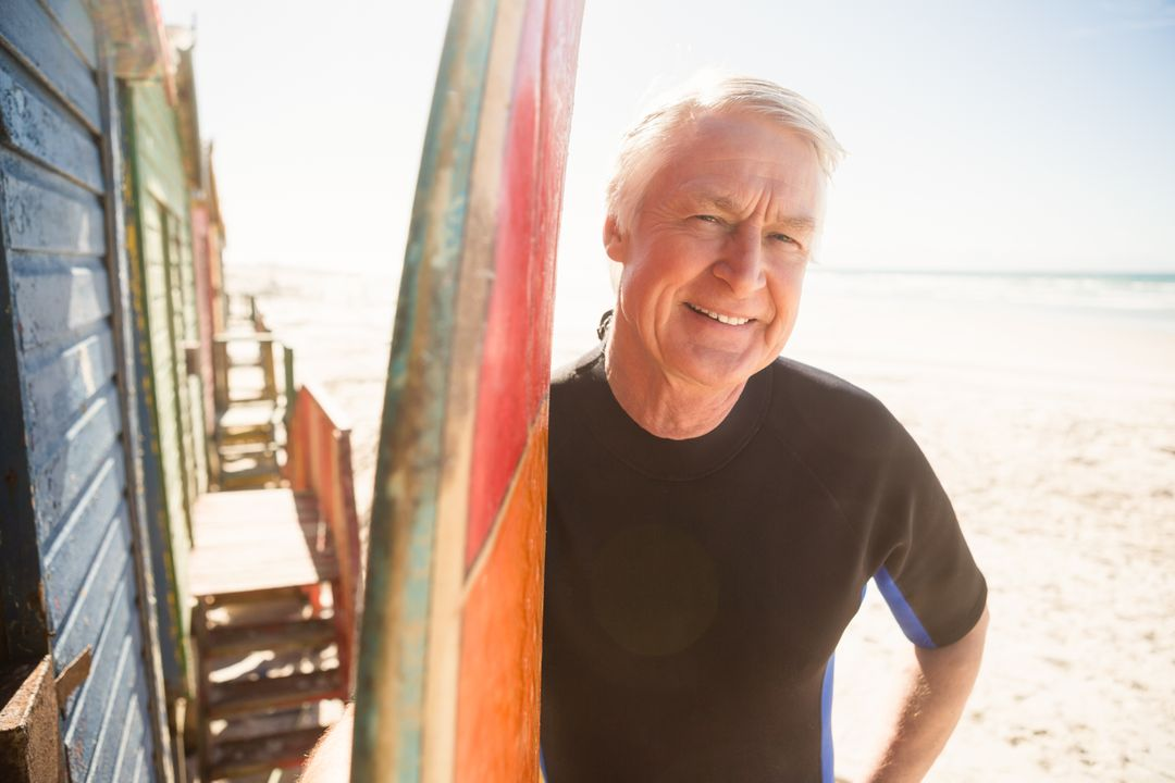 Portrait of smiling senior man standing by surfboard at beach Free Stock Images from PikWizard
