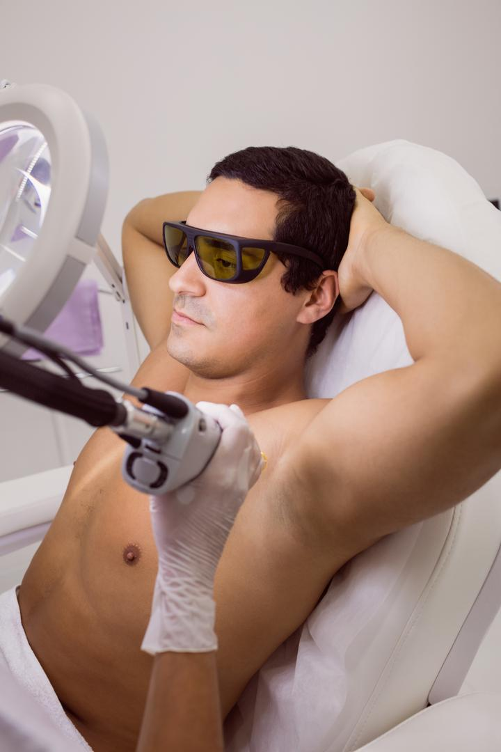 Doctor performing laser hair removal on male patient skin in clinic Free Stock Images from PikWizard