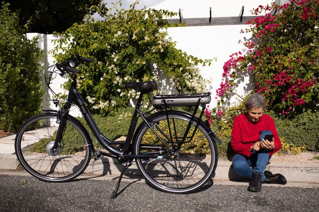 Side view  of a senior Caucasian woman with short grey hair wearing a red sweater sitting on crumb in the street using smartphone, bike next her. Free Stock Images from PikWizard