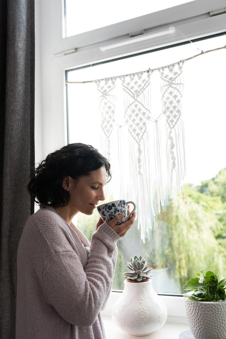 Thoughtful woman standing near the window sill and having coffee cup at home