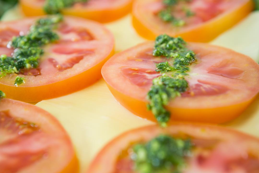 Close-up of tomato slices garnished with green chutney in salad