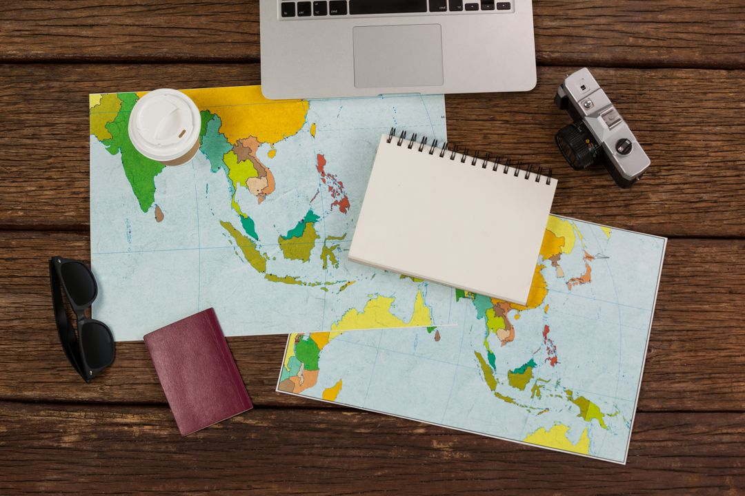 Image of a Laptop, a Map, a Notebook, a Passport, Coffee and Sunglasses on a Desk