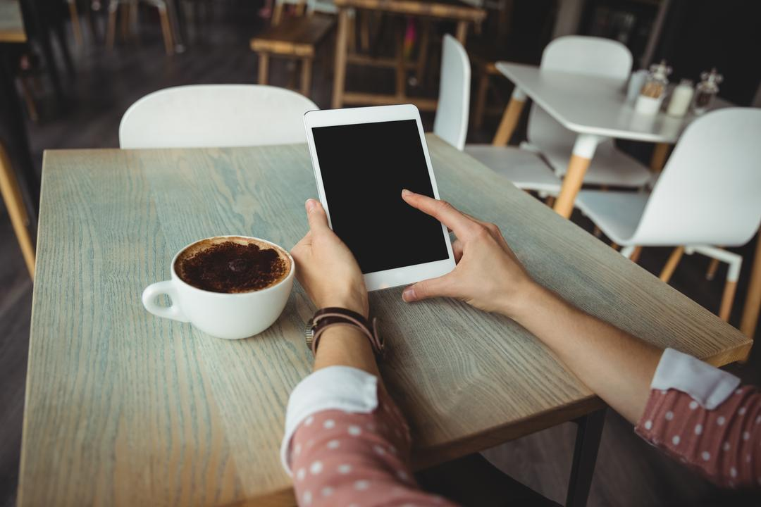 Hand of woman using digital tablet in café Free Stock Images from PikWizard