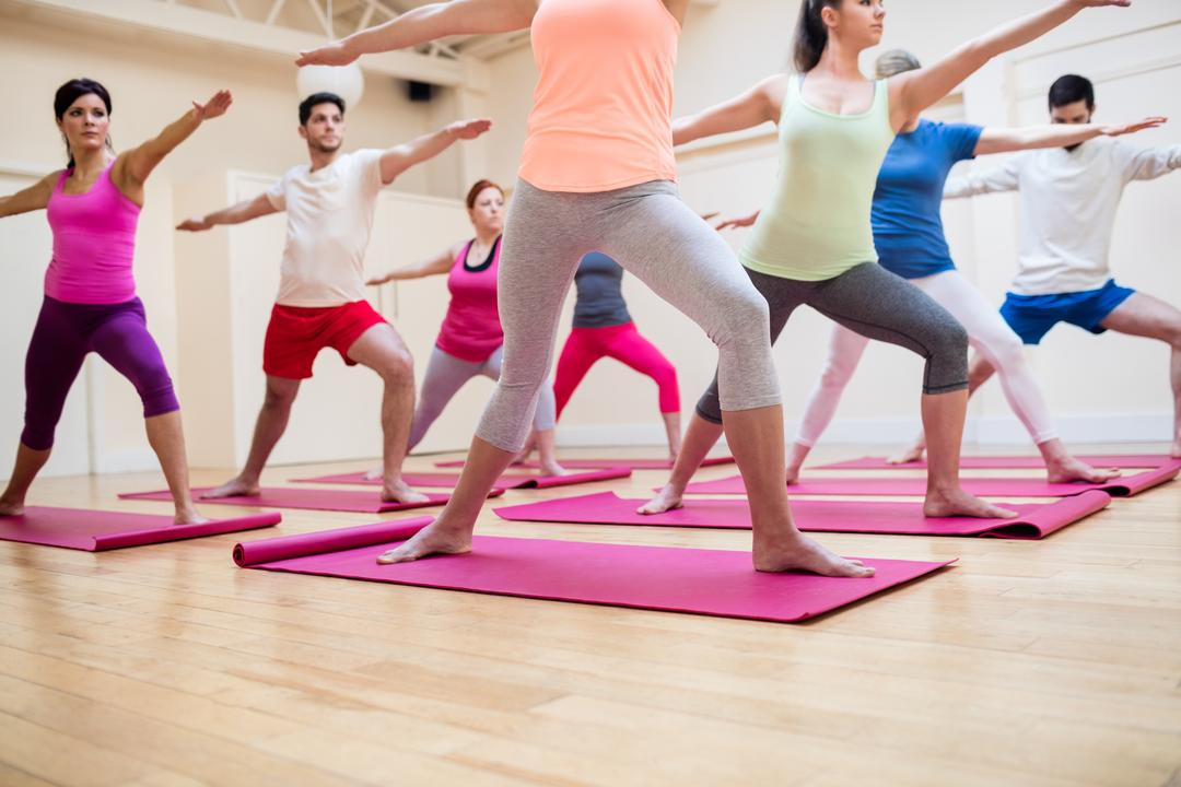 Group of people performing stretching exercise in the fitness studio Free Stock Images from PikWizard