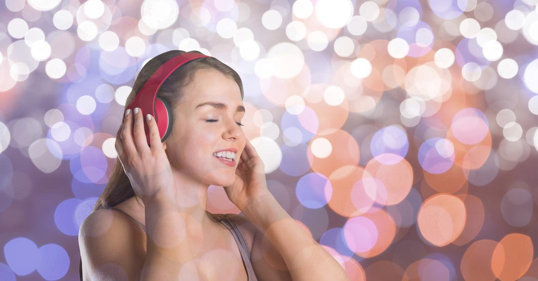 Digital composite of Music artist wearing headphones while singing over bokeh