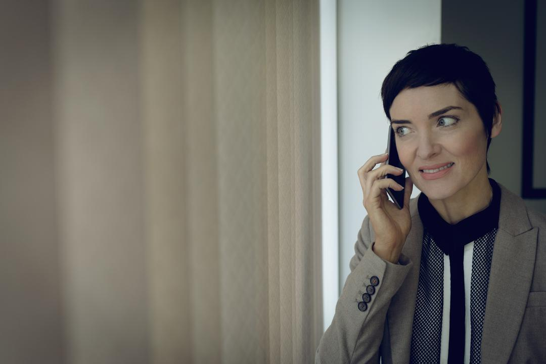 Beautiful businesswoman talking on mobile phone in office