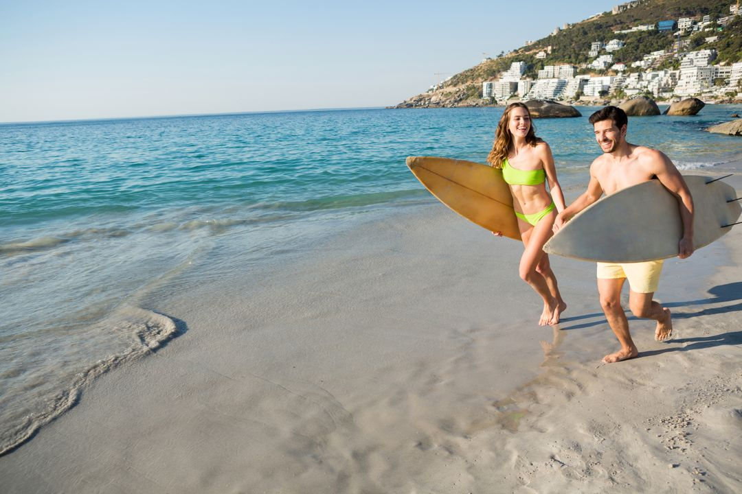 Happy couple running together while holding surfboards at beach on sunny day