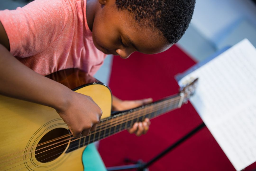 High angle view of boy playing guitar in class at music school Free Stock Images from PikWizard