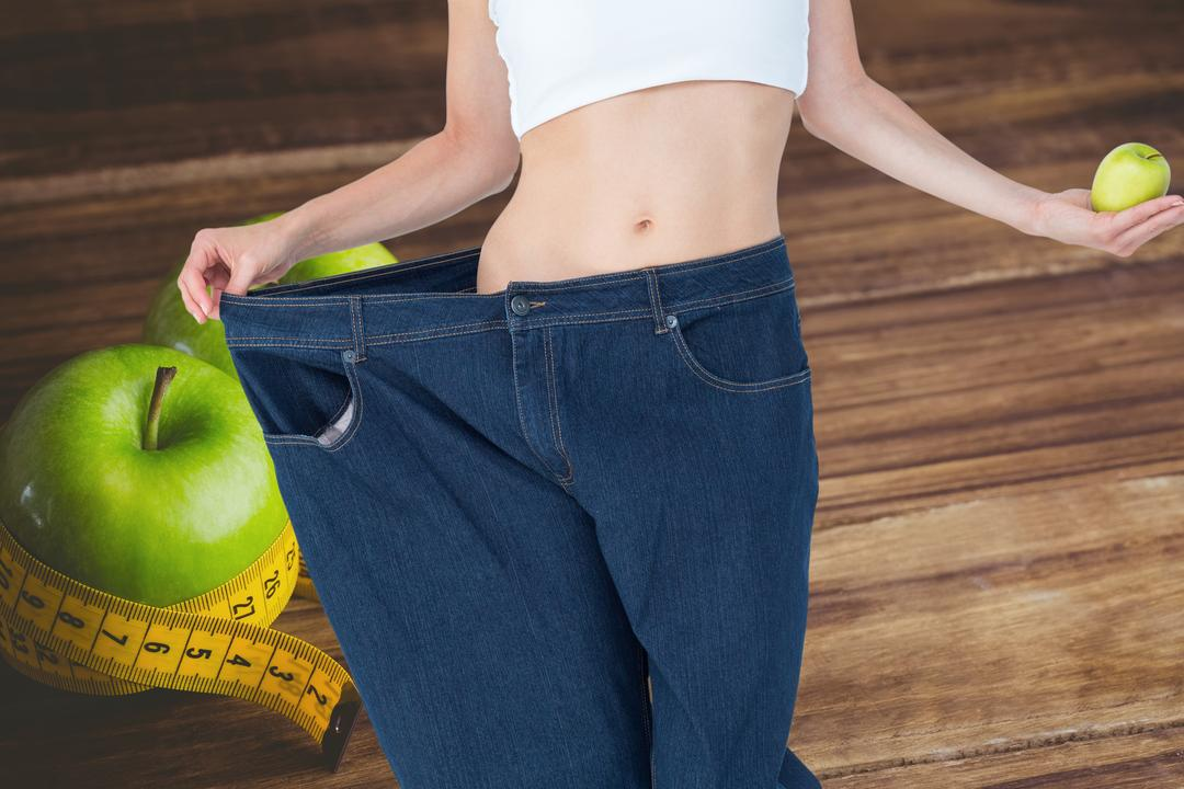 Digital composite of Midsection of woman in loose jeans holding  granny smith apple representing weight loss