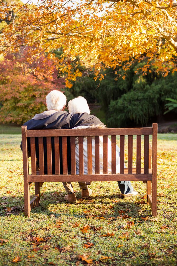 Senior couple embracing on a bench in a park