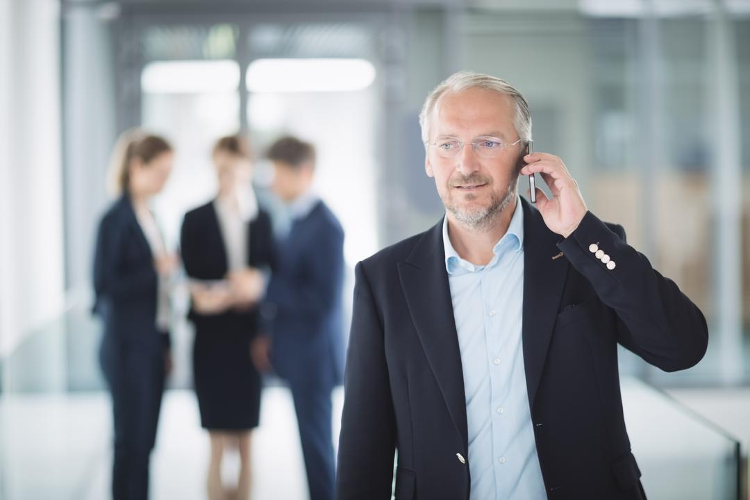 Confident businessman talking on mobile phone in office Free Stock Images from PikWizard