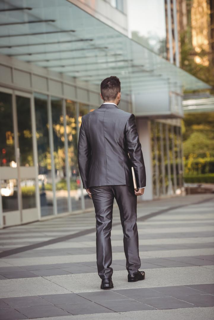 Rear view of businessman with a diary walking in the office campus