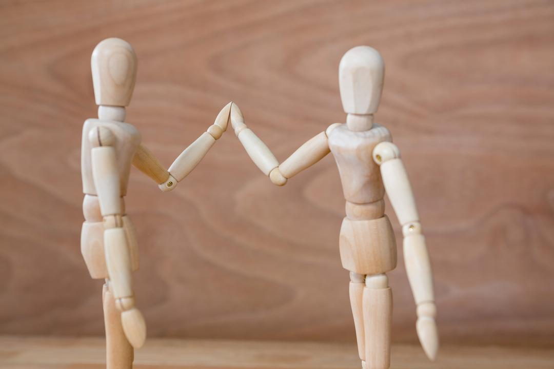Conceptual image of figurine couple holding hands Free Stock Images from PikWizard