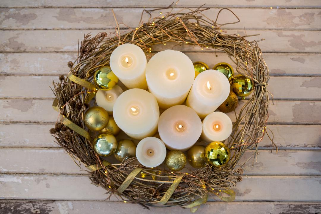 Candles and bauble ball in nest basket on wooden plank during christmas time