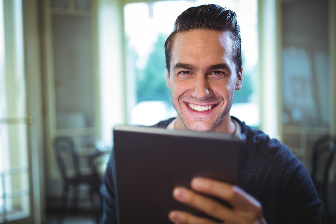 Portrait of smiling man using digital tablet in café