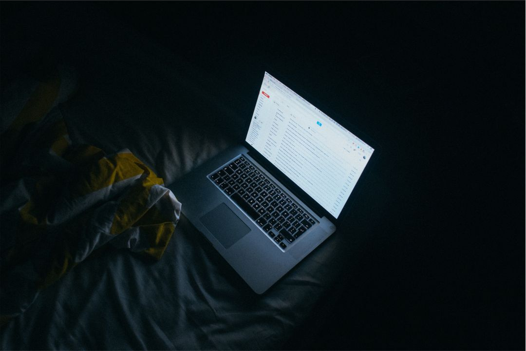 Image of a Laptop on a Bed at Night with a Bright Screen