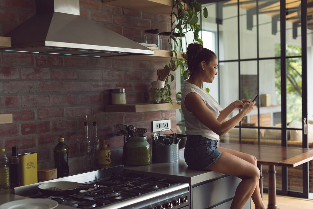 Side view of beautiful woman using mobile phone while sitting on worktop in kitchen at comfortable home