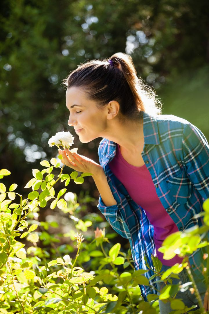 Smiling woman with closed eyes smelling white roses at backyard