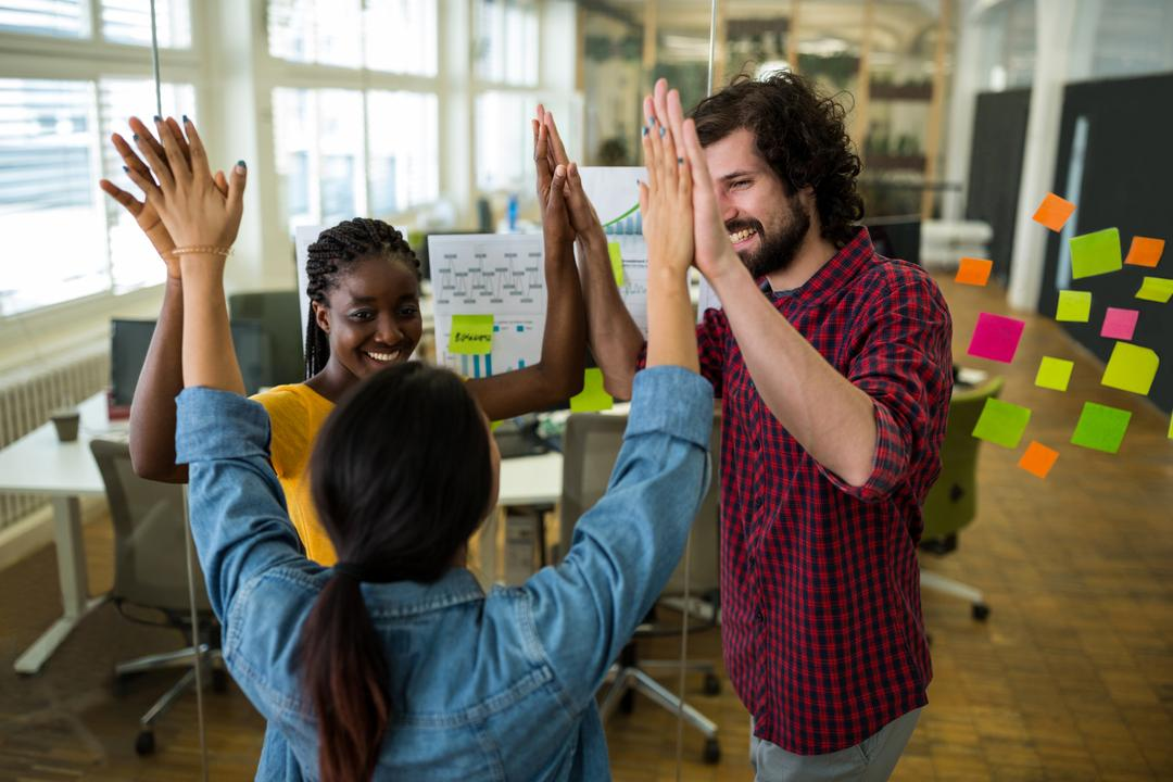 Group of graphic designers giving high five to each other in office