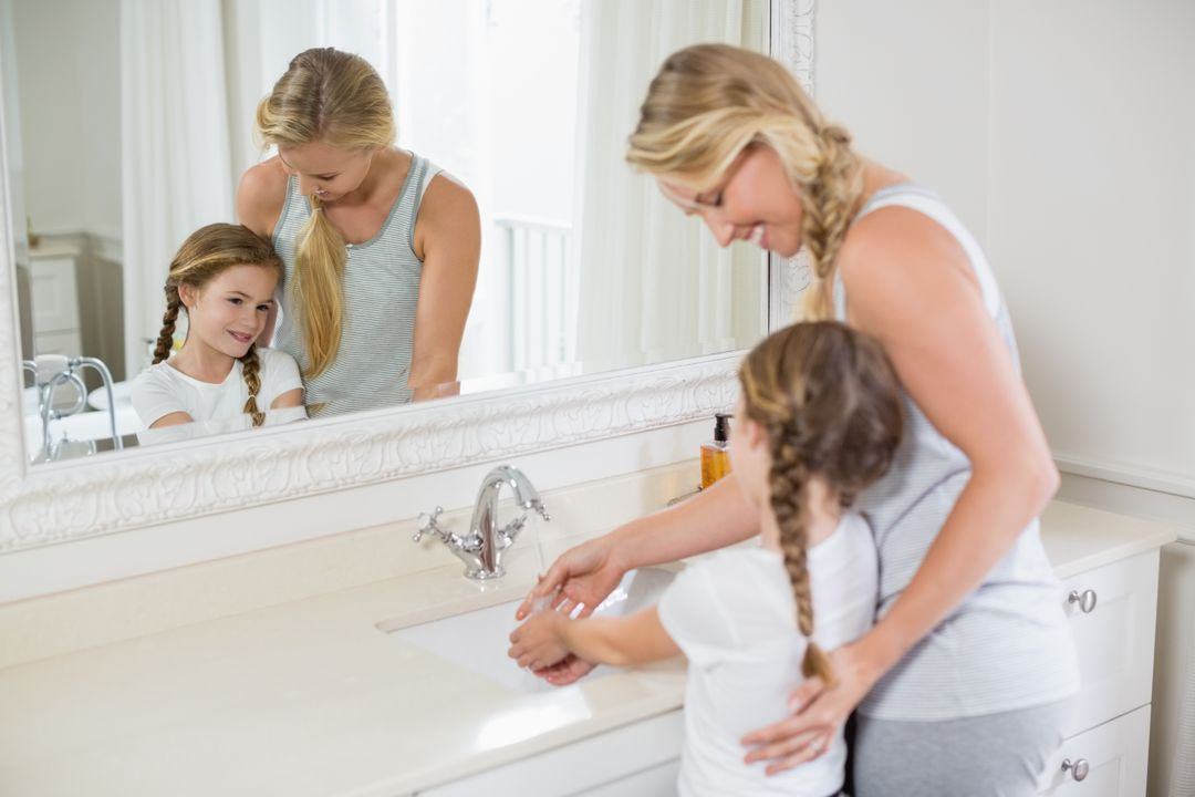 Happy mother and daughter washing hands in bathroom sink at home
