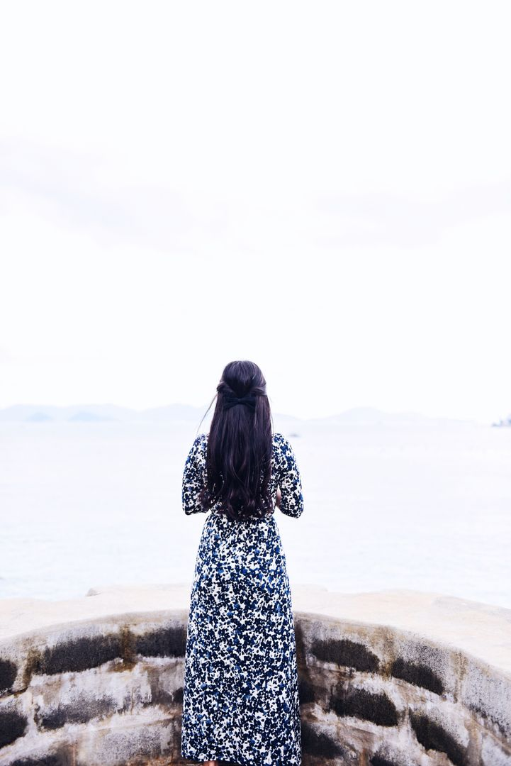 Woman in Black and White Floral Dress Standing in Front of Ocean View during Daytime