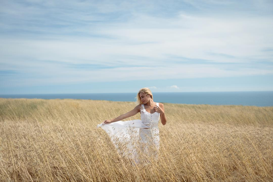 Carefree blonde woman standing in field